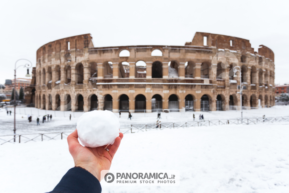 A lovely day of snow in Rome, Italy, 26th February 2018: a view of a snowball in my hand behind the Colosseum under the snow
